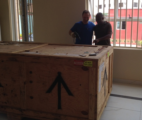 Stephen Small with Chike Chuka opening the Accu SPINA shipping crate